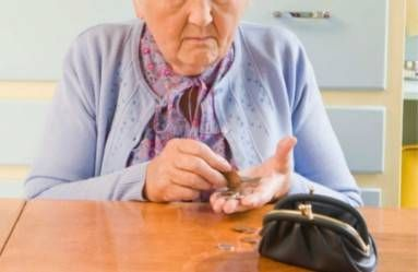 worried elderly woman counting coins