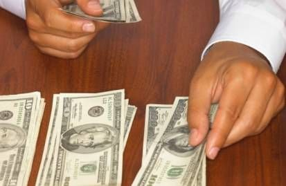 Hands counting cash into different stacks