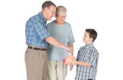 grandparents putting money into kids piggy bank