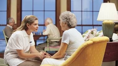 a nurse speaking to a woman in a nursing home