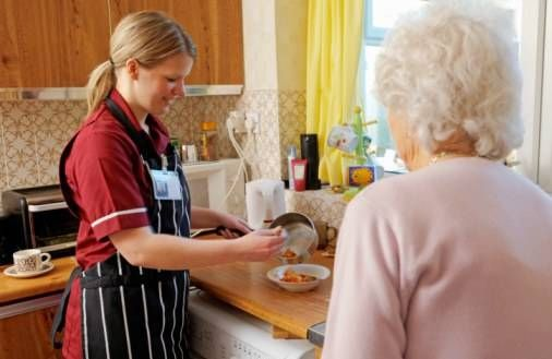 home health care aid with senior woman in kitchen
