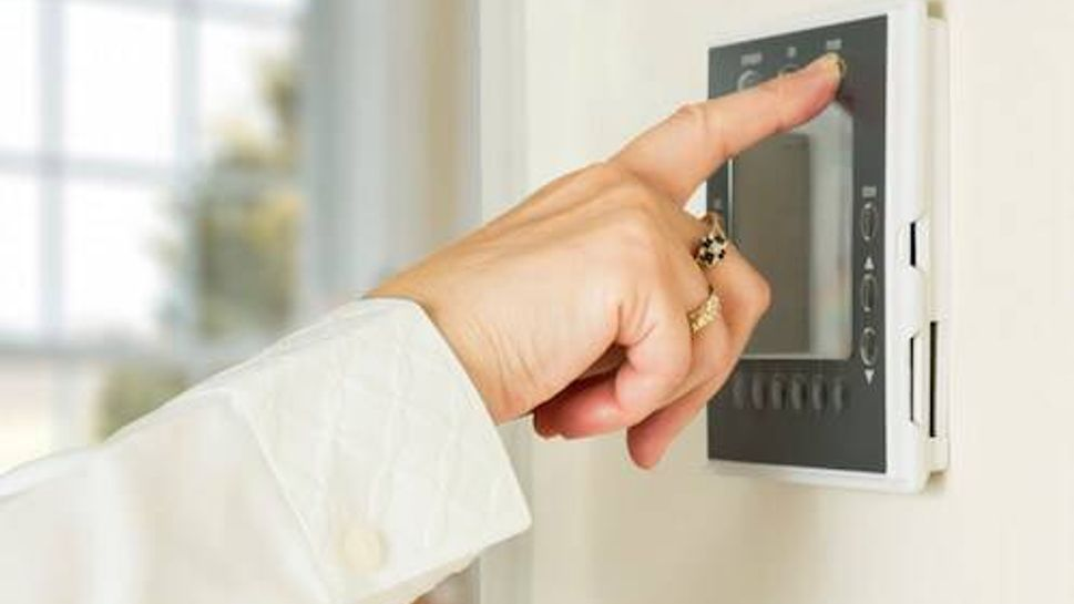 Caucasian lady pressing modern thermostat