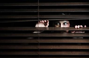 A woman peeks out from beneath blinds, looking scared.