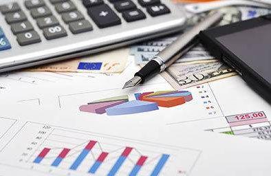 Financial charts, calculator and pen