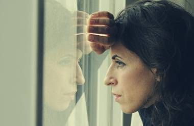 Distressed woman looking out window