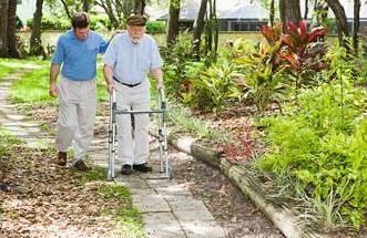 middle aged son walking with his father in a walker