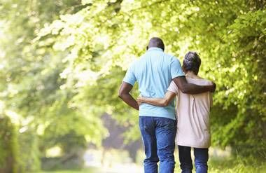 mature couple walking in wildnerness with arms around each other