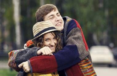 Two millennials hugging