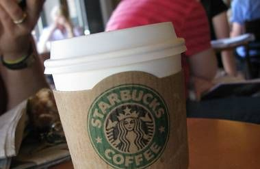 Starbucks coffee cup with customers in the background
