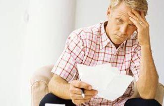 a man looking at bills