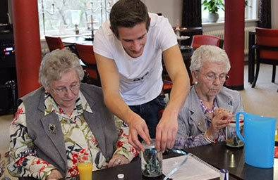 Student Onno Selbach interacts with two nursing home residents at Humanitas
