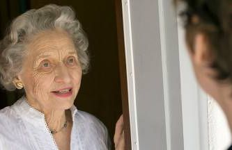 a senior woman opening the door to a visitor