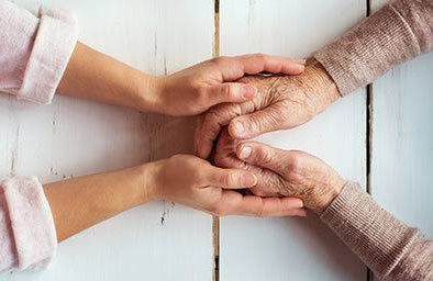 Caregiver holding hands of elderly person