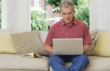 mature man sitting on a couch using a computer