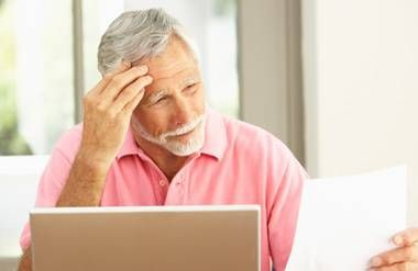 Man looking at finances on paper and computer