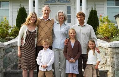 American family standing in front of house grandparents parents children