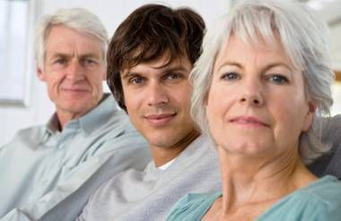 a college-aged son sitting in between grey-haired parents