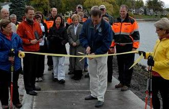 Mike Murtaugh, former mayor of Albert Lea, Minn., opens a new sidewalk.
