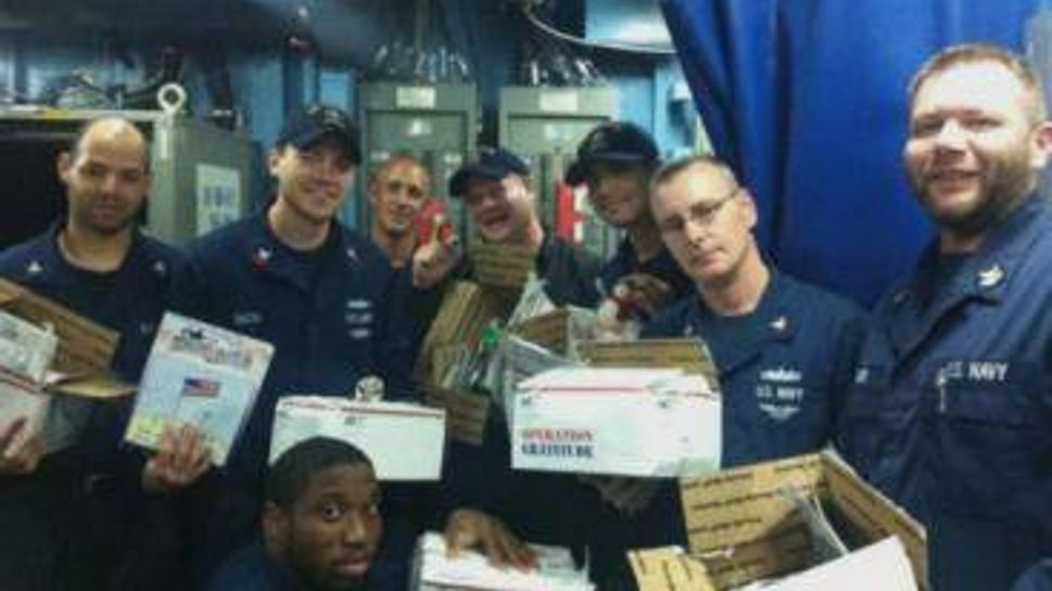U.S. Navy sailors open care packages from Operation Gratitude.
