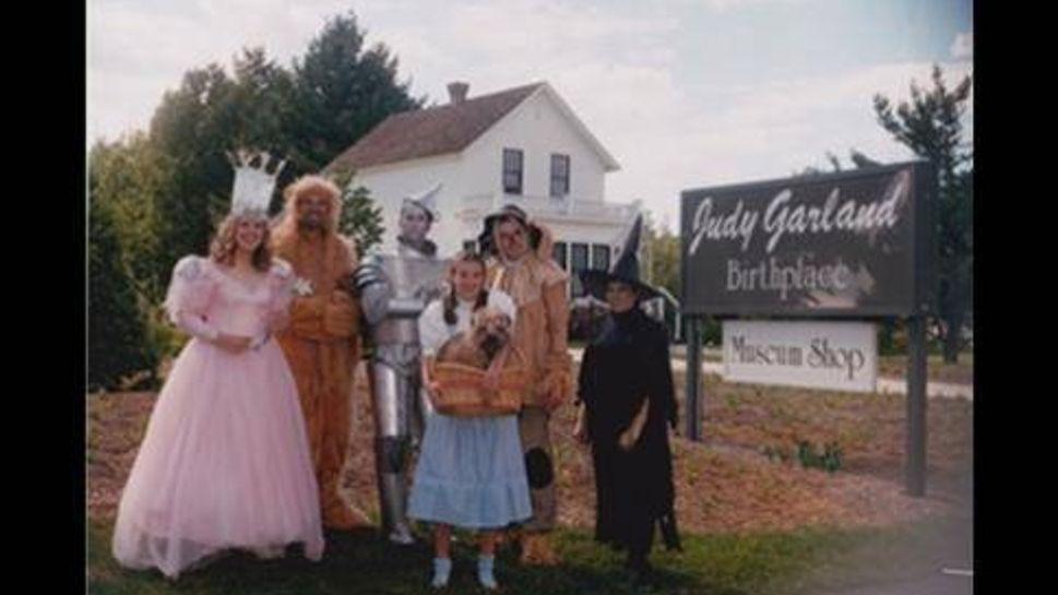 actors dress up as the wizard of oz characters in front of judy garland's house