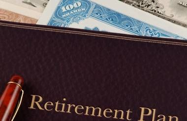 Retirement plan book with pen and papers