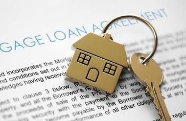Key with house key ring on mortgage loan agreement