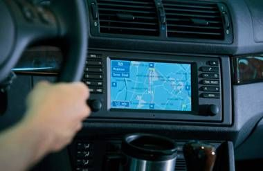 hands on the wheel of a car with a gps