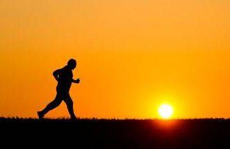 an older man running at sunrise