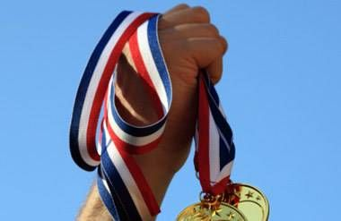 An athlete's hand, holding several gold medals.