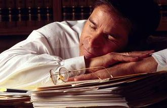 A mature business man takes a nap at his desk to recharge.