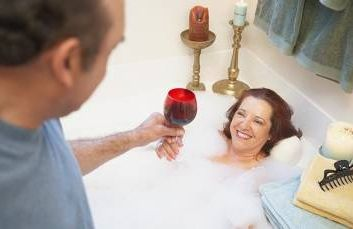 Mature man giving a mature woman a glass of wine in a bathtub