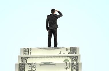 Man standing on top of money stairs