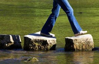a woman walking over stepping stones across a creek