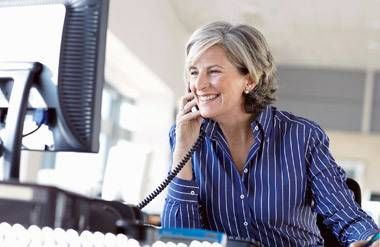 Mature business woman at a desk, talking on the phone