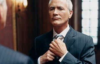 A gray-haired man looking in the mirror while tying his tie.