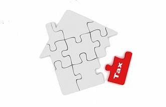 a puzzle of a house with a tax piece in red