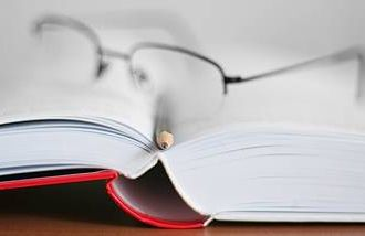 Blurred image of a book and glasses
