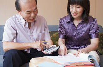 An older Asian couple reviewing their finances for retirement.