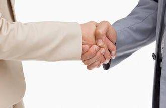 A closeup of a handshake after negotiating a job offer.