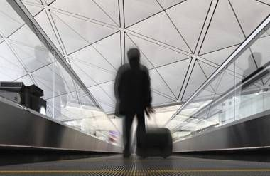 Person walking through airport with suitcase