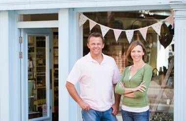 Couple standing in front of their shop