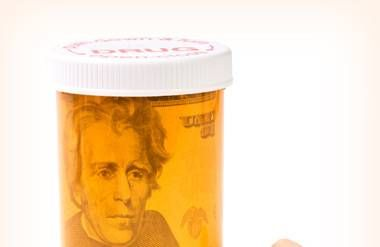 Prescription bottle with pills and money