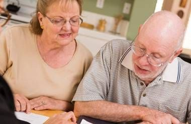 Couple going over papers with financial planner