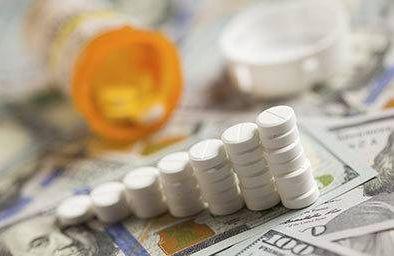 Stacked prescription pills on pile of money