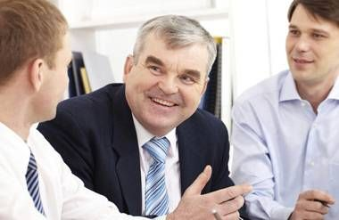 Older man working in office with younger employees