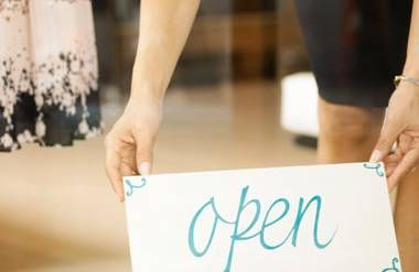 Woman putting open sign into store window