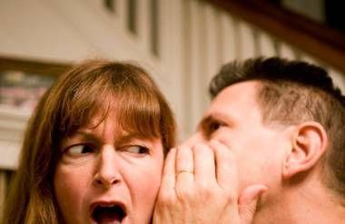 Man telling woman a secret