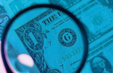 Magnifying glass inspecting US dollar bills
