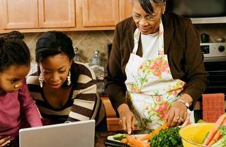 african american grandmother cooking with grand daughters