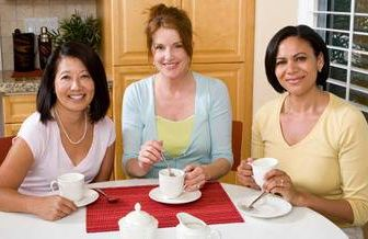 three women friends having coffee at the kitchen table